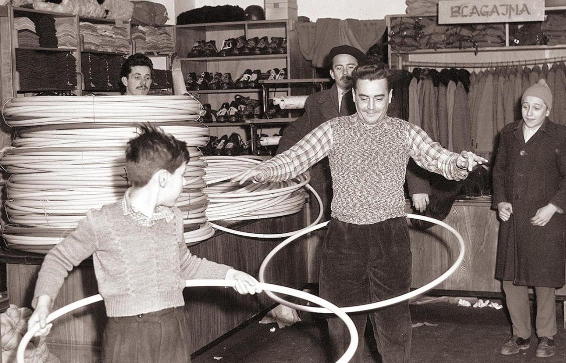 Photographie en noir et blanc d'un homme et d'un garçon faisant tournoyer de gros cerceaux autour de leurs hanches dans un magasin de vêtements.