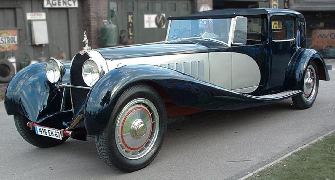 Photographie en couleur d'une longue voiture ancienne argent et noir.