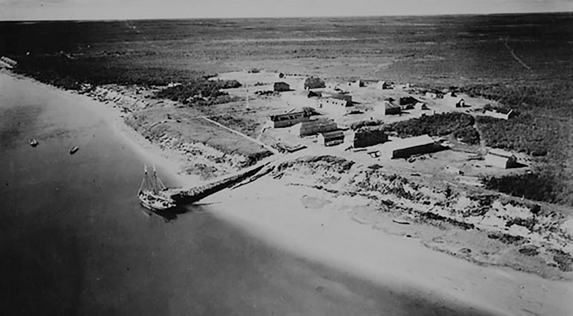 Photographie en noir et blanc montrant la vue aérienne d'une vaste terre inoccupée et d'établissements de style militaire situés près de la rive.