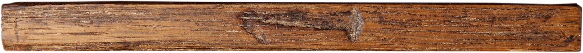 Tige de bois érodée au milieu de laquelle est gravé un gros chiffre « 1 ».