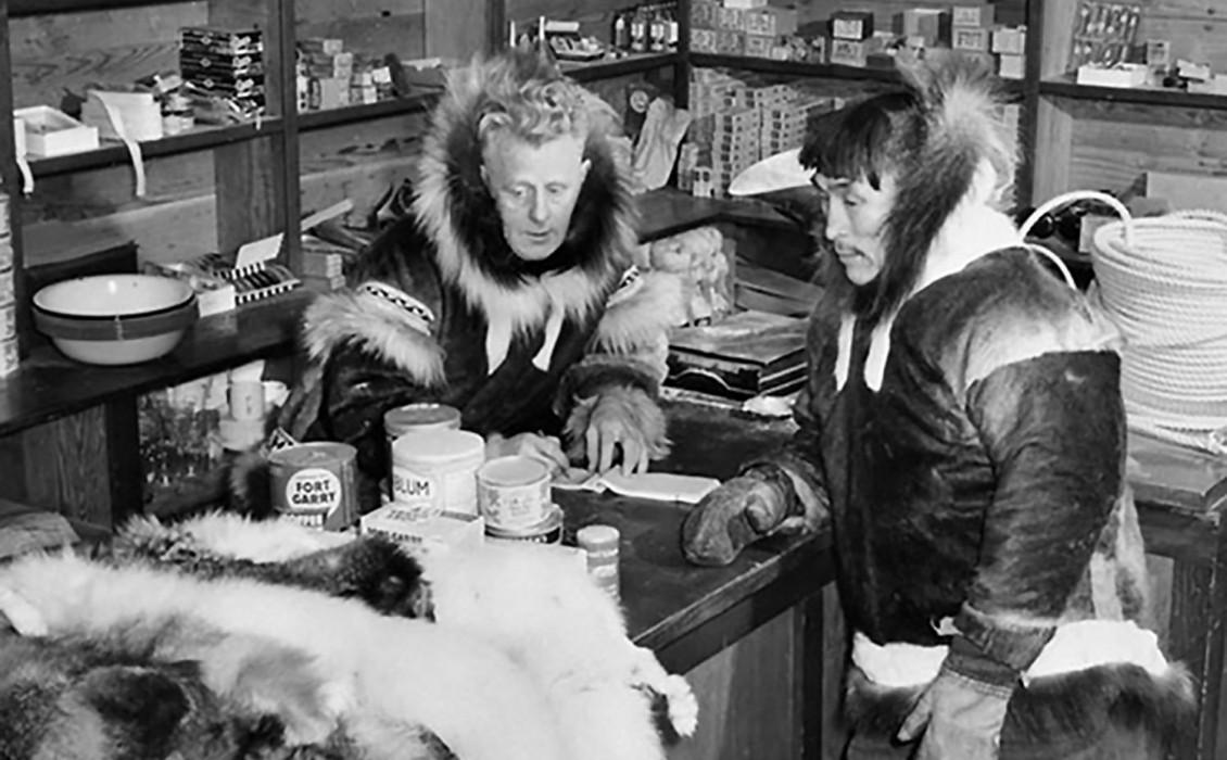Photographie en noir et blanc montrant un homme blanc et un homme autochtone vêtus d'un parka dans une pièce remplie de provisions.