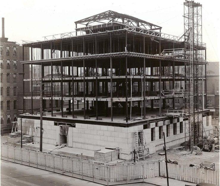 Photographie en noir et blanc de la charpente d'un immeuble carré de quelques étages dont le bas est en blocs de pierre et le reste en poutres d'acier.