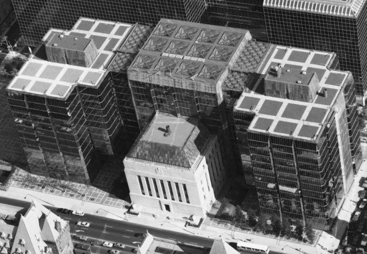Photographie de trois tours de verre annexées à un immeuble en pierre, de forme carrée.