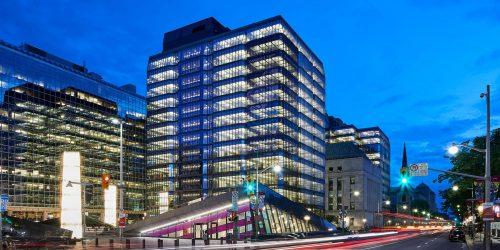 Vieil immeuble en pierre, de forme carrée, flanqué de deux tours de verre illuminées.