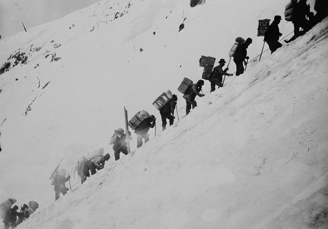 Photo noir et blanc montrant des hommes avec de gros sacs à dos gravissant une montagne enneigée