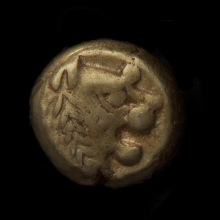 Pièce épaisse de couleur or pâle représentant une tête de lion rudimentaire, de profil